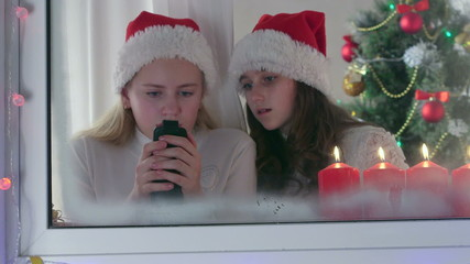 Two girls typing greeting text messages near Christmas tree