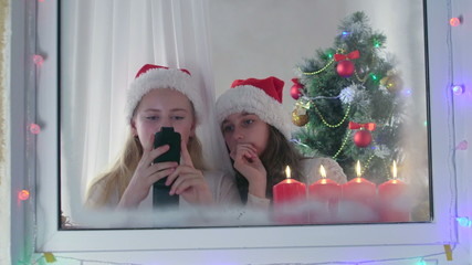 Girls in santa hats sending greeting text messages for Christmas