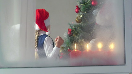 Children decorating a Christmas tree at home view through window