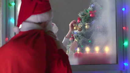 Santa Claus looking through window at children