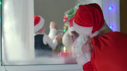 Santa Claus knocking at window and looking at children