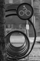 Looking through the loops of a black and white bicycle rack