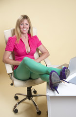 Secretary at desk wearing green tights showing cleavage