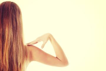 Beautiful topless woman touching her shoulder.