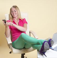 Secretary feet on desk wearing green tights using phone