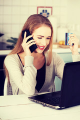 Beautiful caucasian woman talking through phone and working with
