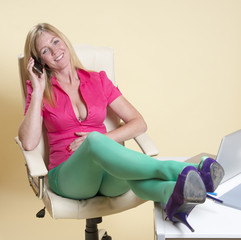 Secretary at desk wearing green tights using mobil phone