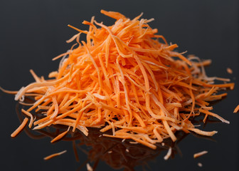 Fresh grated carrots on a black background