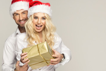 Beautiful smiling couple in santa claus hats with presents