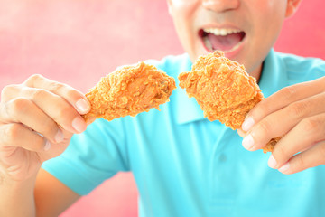 A man with opening mouth about to eat deep fried chicken legs or