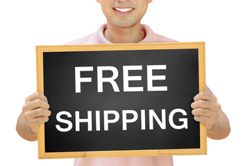 Free shipping sign on blackboard held by smiling man