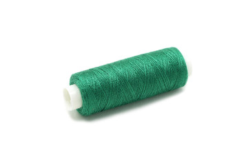 spool of thread of green color on a white background