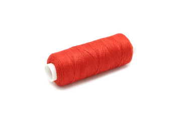 spool of thread of red color on a white background