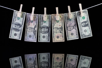Dirty US dollar banknotes hanging from a clothesline and reflect