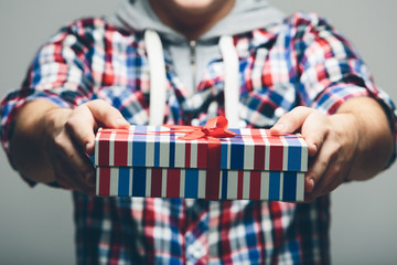 Man Offering Stripe Gift Box with Red Ribbon