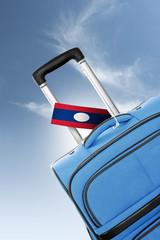 Destination Laos. Blue suitcase with flag.