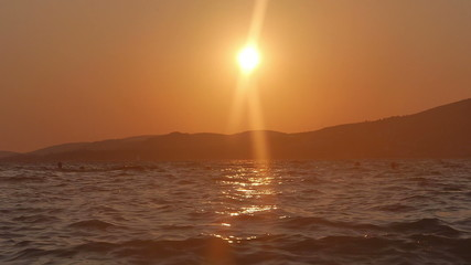 sun reflects in water at beach in croatia during sunset