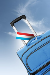Destination Luxembourg. Blue suitcase with flag.