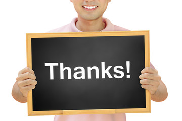Thanks word on blackboard held by smiling man