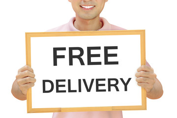 Free delivery sign on whiteboard held by smiling man