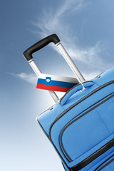 Destination Slovenia. Blue suitcase with flag.