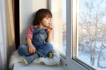 Lovely little boy sits on sill and looks out of window in winter
