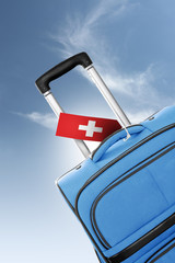 Destination Switzerland. Blue suitcase with flag.