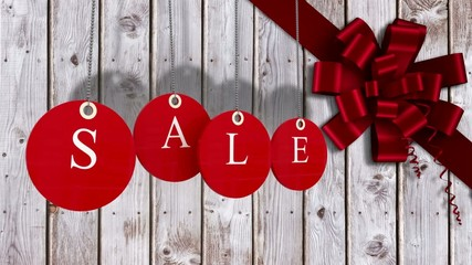 Red sale tags hanging against wood with festive bow
