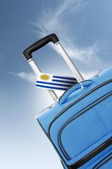 Destination Uruguay. Blue suitcase with flag.