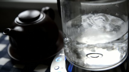 Transparent glass kettle with boiling water