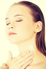 Beautiful woman with healthy skin applying cosmetic cream