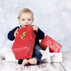 Little baby boy with big christmas presents