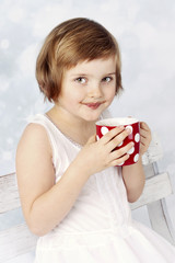 Funny little girl drinking cocoa