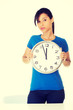 Portrait of shocked woman with clock