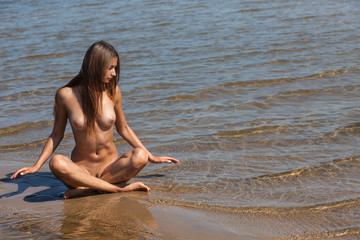 Beautiful young  nude woman by the sea
