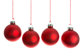 Red Christmas balls hanging at a rope over white