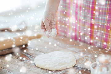 close up of woman hand sprinkling dough with flour