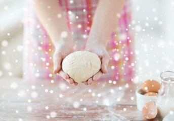 close up of female hands holding bread dough