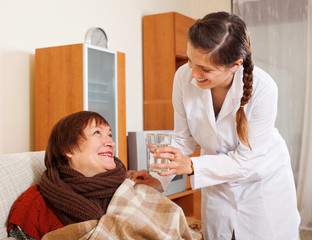 Smiling nurse in uniform caring for happy mature woman