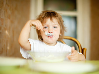 child  eats from plate  with spoon