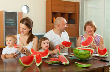 Three generations family eating  watermelon