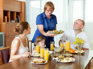 Portrait of happy multigeneration family  eating fish with juice