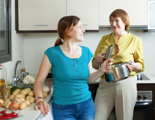 Positive young woman and mature mother in kitchen