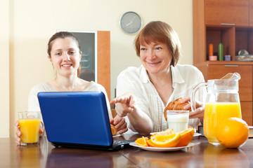 Two happy women using laptop during breakfast