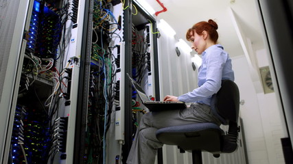 Technician working beside open server