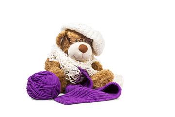 Teddy bear knitting a scarf