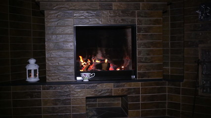 Roaring flames in a modern fireplace with shiny slate framing
