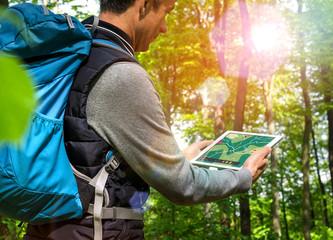 Wanderer mit Tablet-PC beim Wandern Wald Gegenlicht