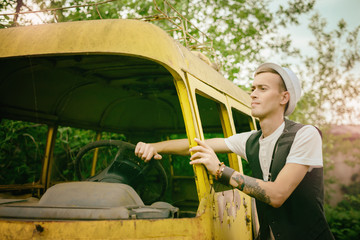 young man hipster tries to get old retro car bus