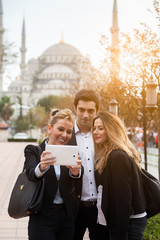 Three business people take Selfie front Blue Mosque Istanbul